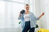 Mosolygó nő táncol, miközben vezeték nélküli hangszórót tart a nappaliban