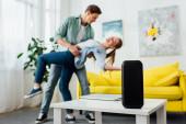 Selektivní zaměření bezdrátového reproduktoru a notebooku na konferenční stolek a usměvavý mladý pár tancující doma