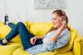 Boční pohled usměvavé dívky ve sluchátkách poslech hudby na gauči
