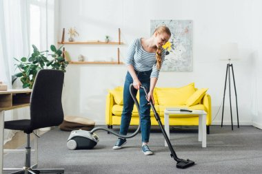 Smiling woman cleaning carpet with vacuum cleaner in living room