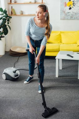Beautiful girl listening music in headphones while cleaning carpet with vacuum cleaner in living room
