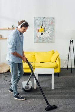 Side view of smiling man in headphones cleaning carpet with vacuum cleaner at home