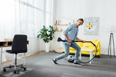 Side view of cheerful man in headphones holding brush of vacuum cleaner in ling room