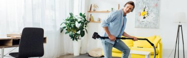 Side view of cheerful man in headphones holding brush of vacuum cleaner in ling room, panoramic shot