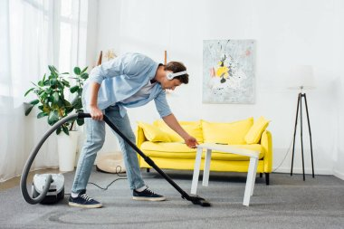 Side view of man in headphones cleaning carpet with vacuum cleaner near coffee table at home
