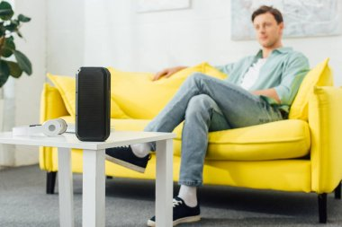 Selective focus of wireless speaker and headphones on coffee table and man sitting on couch in living room