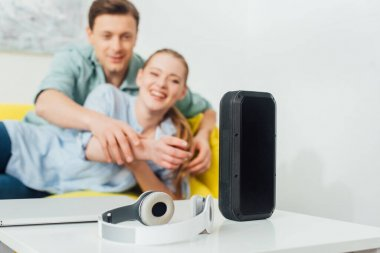 Selective focus of wireless speaker, headphones and laptop on coffee table near cheerful couple on couch at home