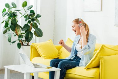 Side view of cheerful girl in headphones singing on couch near laptop and smartphone on coffee table at home
