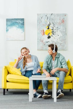 Young couple in headphones sitting on sofa near laptop on coffee table