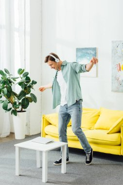 Side view of young man in headphones dancing near laptop on coffee table in living room