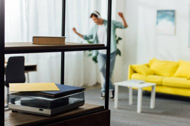 Selective focus of book and record player on shelves of cabinet and man in headphones dancing at home