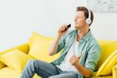 Jóképű férfi fülhallgatóban okostelefont tart otthon a kanapén.