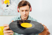 Photo Selective focus of handsome man in headphones holding vinyl record in living room