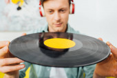 Selective focus of young man in headphones holding vinyl record at home