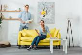 Žena ve sluchátkách s chytrým telefonem a přítel s prachem kartáč s úsměvem na kameru v obývacím pokoji