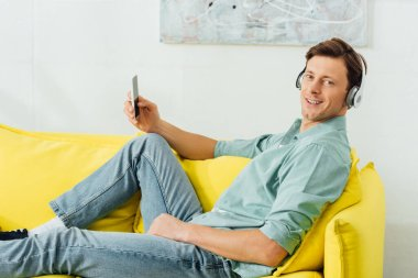 Side view of smiling man in headphones looking at camera while using smartphone on sofa