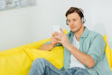 Handsome man in headphones using smartphone on yellow couch at hoe