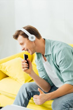Side view of cheerful man in headphones showing thumb up gesture and holding smartphone on sofa
