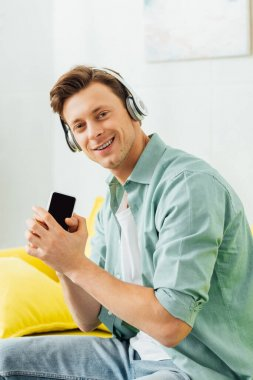 Side view of man in headphones smiling at camera and holding smartphone on couch
