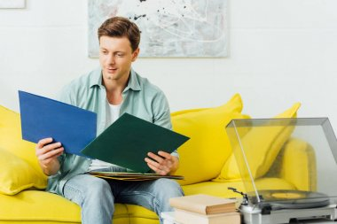 Handsome man holding vinyl records near record player and books on coffee table