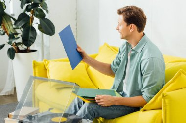 Side view of man holding vinyl records near record player and books on coffee table in living room