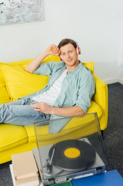 High angle view of record player and books on coffee table and smiling man in headphones sitting on couch at home