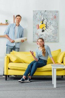 Smiling man with dust brush and woman in headphones with smartphone looking at camera in living room