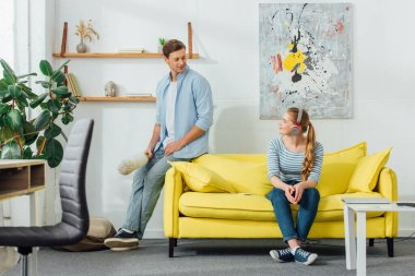 Man with dust brush smiling at girlfriend in headphones on couch in living room