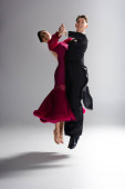 elegant young couple of ballroom dancers in red dress in suit dancing on white
