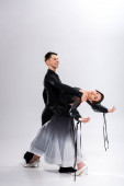 elegant young couple of ballroom dancers in black outfit dancing on white