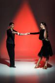elegáns fiatal pár báli táncosok táncolnak piros fényben