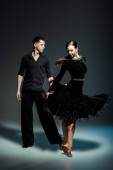 elegant young couple of ballroom dancers in black outfits dancing in dark