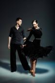 elegáns fiatal pár báli táncosok fekete ruhák táncolnak a sötétben