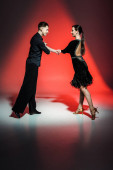 elegant young couple of ballroom dancers in black outfits dancing in red light