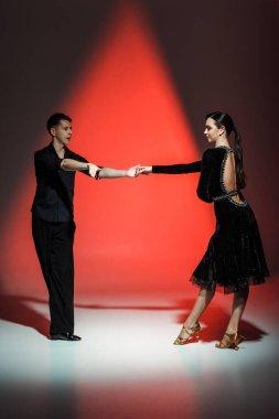 Elegant young couple of ballroom dancers dancing in red light stock vector