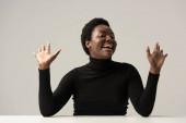 vzrušený africký americký žena v černý rolák sedí u stolu izolovaný na šedé