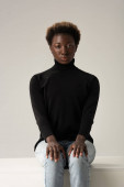 african american girl in jeans and black turtleneck sitting on white cube isolated on grey