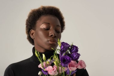beautiful african american woman in black turtleneck holding eustoma flowers isolated on grey