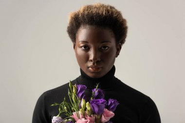 african american girl in black turtleneck holding eustoma flowers isolated on grey