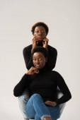 přemýšlivé africké americké ženy v černých rolácích izolované na šedé