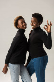 Fotografie smiling african american girls in black turtlenecks showing ok sign isolated on grey