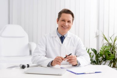 Smiling otolaryngologist looking at camera while sitting ant workplace near otoscope, laptop and clipboard stock vector