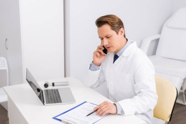 serious ent physician talking on smartphone while sitting at workplace near clipboard, laptop and otoscope