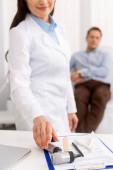 abgeschnittene Ansicht eines lächelnden Arztes, der Otoskop nimmt, und eines Patienten, der im Behandlungsstuhl im Hintergrund sitzt