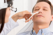 cropped view of otolaryngologist examining nose of handsome man with nasal speculum