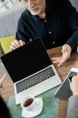 abgeschnittene Ansicht eines Geschäftsmannes, der in der Nähe eines Laptops sitzt und mit einer Geschäftsfrau während eines Geschäftstreffens spricht