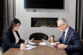 boční pohled na podnikatele pomocí notebooku a asijské podnikatelky dělá papírování během obchodní schůzky