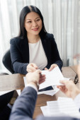 cropped view of businessman giving paper and pen to smiling asian businesswoman during business meeting