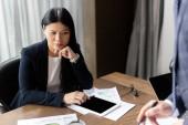 Fotografie oříznutý pohled na podnikatele a zamyšlenou asijskou podnikatelku během obchodní schůzky