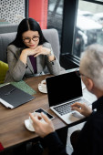 selective focus of asian businesswoman talking with businessman in cafe